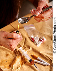 Girl addict with heroin spoon and lighter.