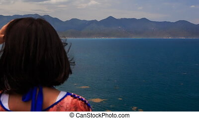 girl admires scenery of seascape turns to camera against sea...