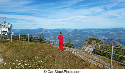 girl admiring mountain landscape from above
