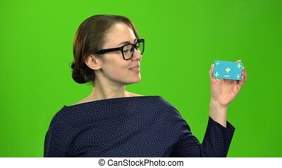 Girl advertises a card and shows a thumbs up. Green screen