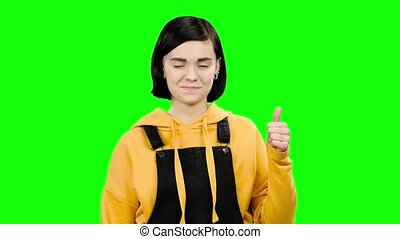 Girl advertises the goods and shows a thumbs up. Green screen