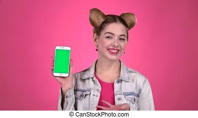 Girl advertises the phone. Pink background. Slow motion