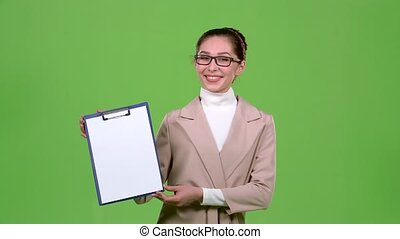 Girl advertising agent shows important information on the tablet, she is smiling and affable. Green screen. Slow motion