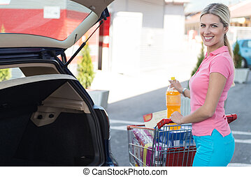 Girl After Shopping Loading Grocery in Car Supermarket