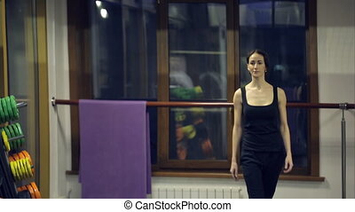 Girl after the workout goes ahead and dissolve hair in an empty gym.