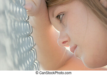 pretty teen girl with wishful look, leaning against chain link fence. backlit, shallow dof.
