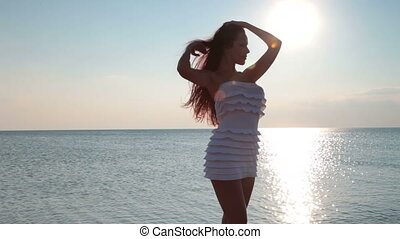 girl against the sunlight - silhouette of young woman posing...