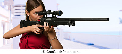 Girl Aiming With Gun at the beach