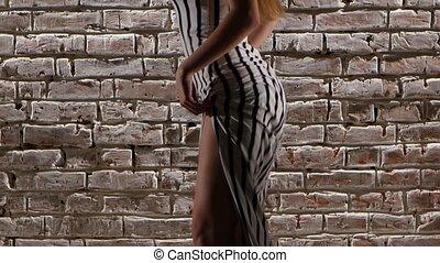 Girl alluring in heels dancing to twerk against a brick wall. Close up