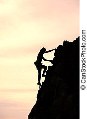 Girl alone conquer the summit during a climb in a fantastic mountain landscape at sunset