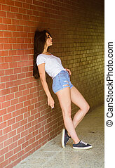 Girl alone smoking brick wall background. Woman lean on wall hang out in porch. She waiting for someone. Underground culture. Girl attractive brunette relaxing hang out underground crossing or subway