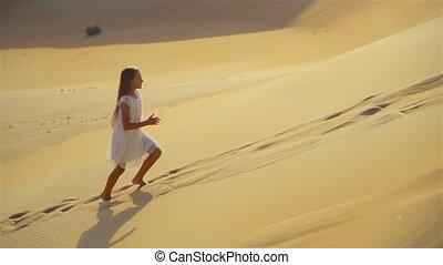 Little girl enjoys vacation in dunes in desert in United Arab Emirates