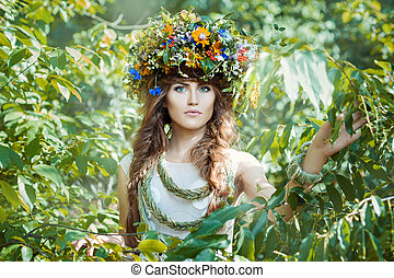 Girl among leaves trees with a wreath on his head.