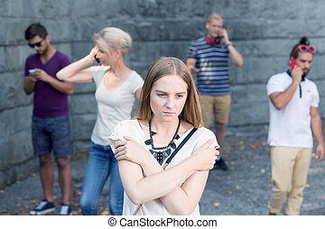 Girl among people with phones - Sad girl standing among...