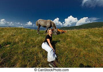 girl and a couple of horses in nature