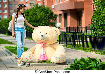 girl and a huge teddy bear on the street in the city