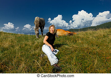 girl and a pair of horses on the background of the sky