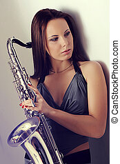 girl and a saxophone - girl standing against a wall and...