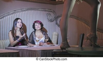 Girl and adult woman sit at table, look on dancer on table. Burlesque. Wine