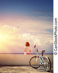 Girl and Bicycle - One bicycle and a little girl sitting on...