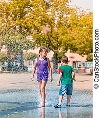 Girl and boy are enjoying fountain