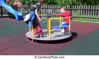 Girl and boy at playground. Children play on roundabout