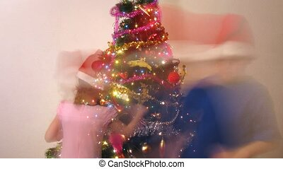 Girl and boy decorate New Year tree by New Year in hats of Santa Claus