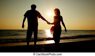 Girl and boy go at beach holding hands for sea, silhouettes on sunset, part1