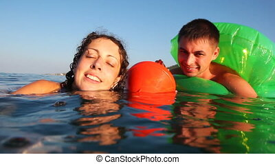 Girl and boy in inflatable disc is afraid, cannot swim, cling buoy into sea