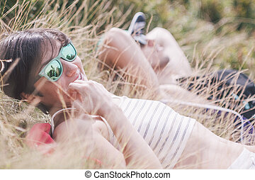 girl and boy laying in the grass in the mountains