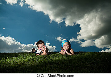 Girl and boy laying on the grass