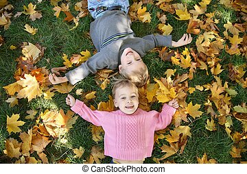 girl and boy lie on the grass