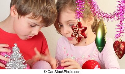 Girl and boy play with christmas-tree decoration - Girl and...
