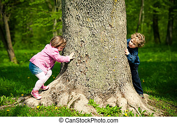 girl and boy playing hide and seek