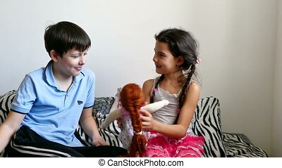 girl and boy playing with a doll sitting on a bed