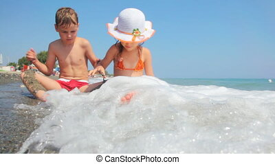 Girl and boy sit at edge of sea shore, play with sand