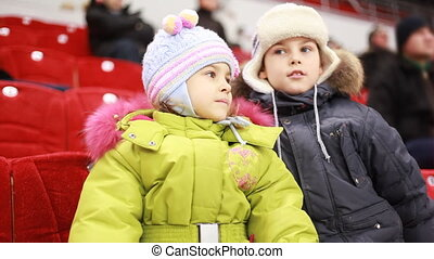 girl and boy sit on armchairs, attentively watch hockey match, then he tells something to it
