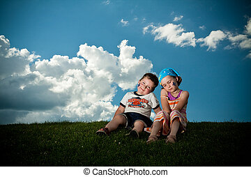 Girl and boy sitting on the grass on the grass