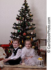 Girl and boy sitting under Christmas tree