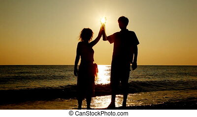 Girl and boy stand holding in hands sun on seashore, silhouettes at sunset, part5