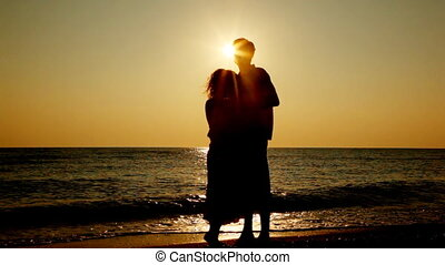 Girl and boy stand hugging on beach, silhouettes at sunset, part2