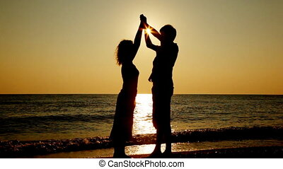 Girl and boy stand joining hands raised up on seashore, silhouettes at sunset, part4