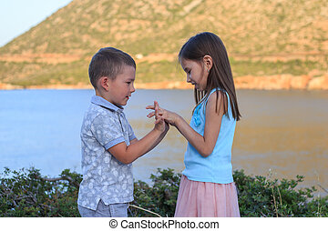 Girl and boy together outdoors. small brother playing with older sister