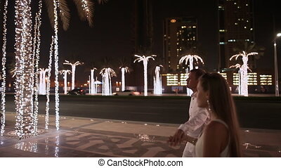 Girl and boy walking on the street the night Dubai. Among the glowing palms trees.