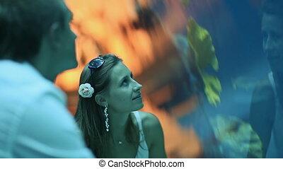 Girl and boy watching fish in an aquarium.