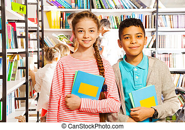 Girl and boy with books standing in library