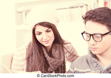 girl and boy with glasses reading together on vintage ...