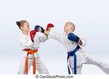 Girl and boy with the overlays on the hands are training strikes