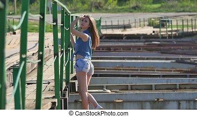 Girl and bridge. Beautiful lifestyle sexy girl is standing...