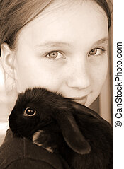 Girl and bunny - Portrait of a young girl holding a black...